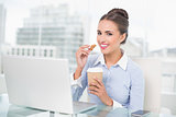 Smiling brunette businesswoman holding cookie