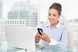 Smiling brunette businesswoman looking at smartphone