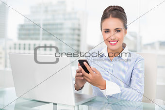 Smiling brunette businesswoman holding smartphone