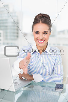 Smiling brunette businesswoman extending arm
