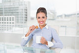 Smiling brunette businesswoman holding mug and cookie