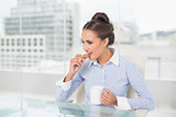 Content brunette businesswoman eating cookie
