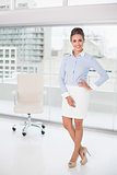 Smiling brunette businesswoman standing feet crossed