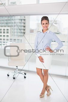 Smiling brunette businesswoman standing feet crossed