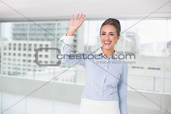 Smiling brunette businesswoman standing and waving