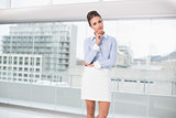 Thoughtful brunette businesswoman standing