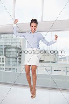 Excited brunette businesswoman cheering