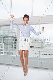 Excited brunette businesswoman cheering