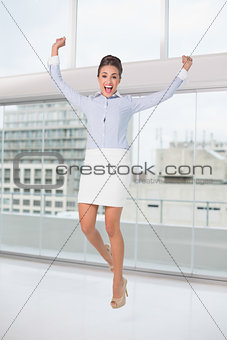 Excited brunette businesswoman jumping and cheering