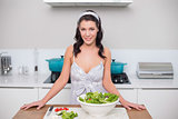 Smiling pretty brunette making salad