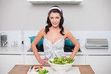 Happy pretty brunette making salad
