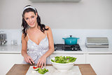 Cheerful pretty brunette chopping vegetables
