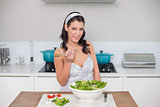 Smiling pretty brunette preparing healthy salad