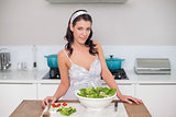 Peaceful pretty brunette preparing healthy salad