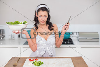 Serious pretty brunette holding healthy salad