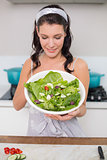 Smiling pretty brunette showing healthy salad