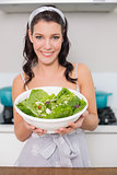 Cheerful pretty brunette showing healthy salad