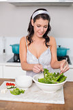 Happy pretty brunette mixing healthy salad