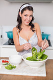 Cheerful pretty brunette mixing healthy salad