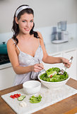 Smiling pretty brunette mixing healthy salad
