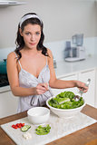 Peaceful pretty brunette mixing healthy salad