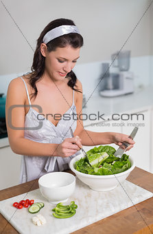 Focused pretty brunette mixing healthy salad
