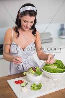 Cheerful cute brunette preparing healthy salad