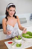 Smiling cute brunette preparing healthy salad