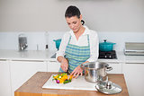Focused pretty woman chopping vegetables