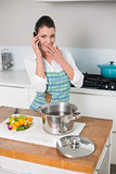 Surprised pretty woman wearing apron having a call