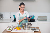 Cheerful gorgeous woman wearing apron using tablet