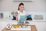 Happy gorgeous woman wearing apron using tablet while cooking
