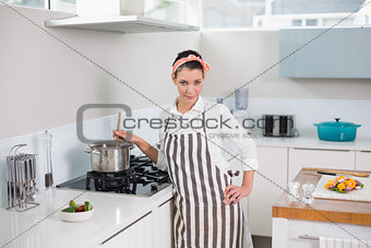 Calm pretty woman with apron cooking