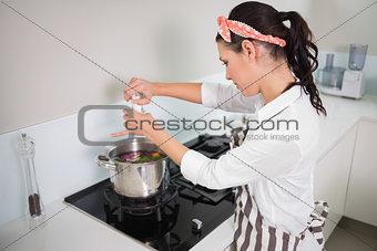 Focused gorgeous cook putting salt on vegetables