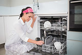 Smiling charming woman using dish washer