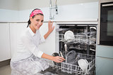 Cheerful charming woman using dish washer