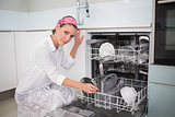Serious charming woman using dish washer