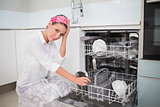 Worried charming woman using dish washer