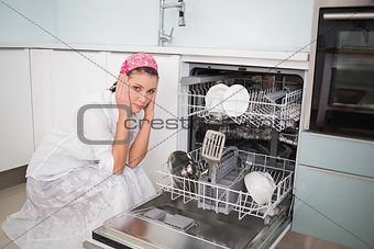 Anxious charming woman sitting next to dish washer