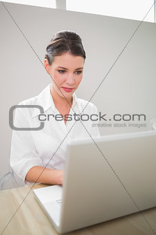 Focused charming businesswoman using laptop