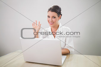 Waving gorgeous businesswoman using laptop