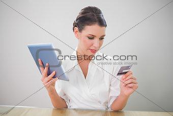 Calm pretty businesswoman shopping online
