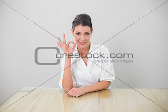 Smiling brown haired businesswoman making okay gesture