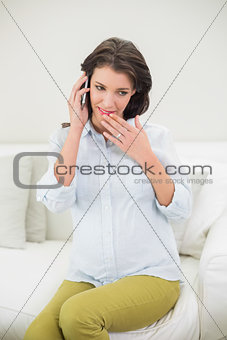 Attractive pregnant brown haired woman making a phone call