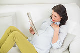 Attentive pregnant brown haired woman reading a newspaper