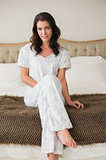 Relaxed pretty brown haired woman sitting on a bed