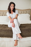 Peaceful pretty brown haired woman sitting on a bed