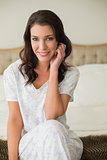 Smiling pretty brown haired woman sitting on a bed