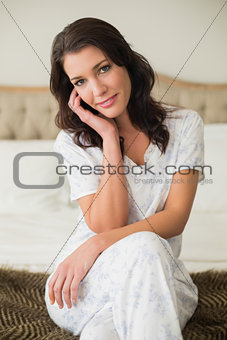 Thoughtful pretty brown haired woman sitting on a bed