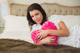 Peaceful pretty brown haired woman hugging a heart shaped pillow